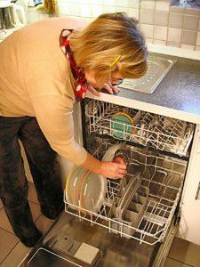 אישה מכניסה כלים מלוכלכים